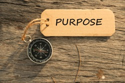 Magnetic compass and text PURPOSE written on paper tag at outdoor. Conceptual image with selective focus