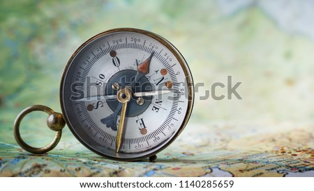 Magnetic compass on world map.Travel, geography, navigation, tourism and exploration concept background. Macro photo. Very shallow focus. #1140285659