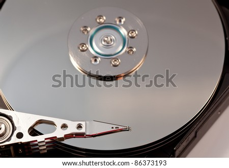 Magnetic disc inside a computer hd unit showing mirror surface of the magnetic discs and read write head