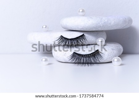 Magnetic fake artificial eyelashes and pearl on white stones. Home eyelash extension, cosmetology tool concept, beauty treatment, improving physical appearance