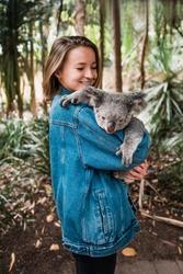 Magnetic island, Australia: Young happy woman holding koala and smiling, noise