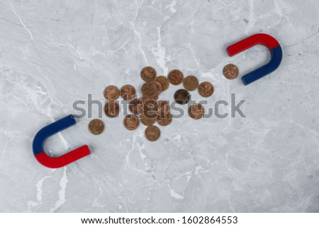 Magnets attracting coins on grey marble table, flat lay