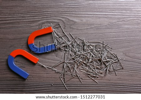 Magnets attracting nails on dark grey wooden background, flat lay #1512277031