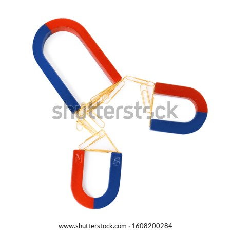 Magnets attracting paper clips on white background, top view