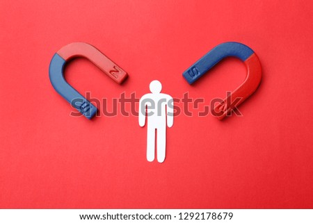 Magnets attracting paper man on color background, top view. Business rivalry concept #1292178679
