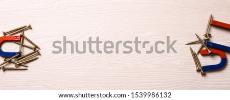 Magnets attracting screws on light wooden background, flat lay. Space for text #1539986132