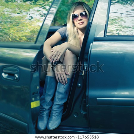 magnificent blonde driver girl with sunglasses sitting in the blue colored car. outdoor shot