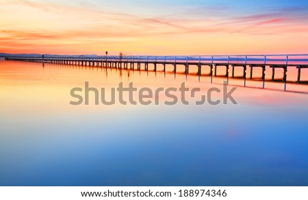 Magnificent colours in the sky, pink towards the north and red towards the south, at idyllic Long Jetty Central Coast, Australia