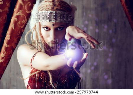 Magnificent fortune teller holding crystal ball. Magic.