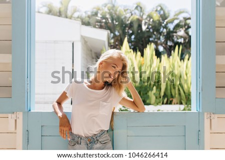 Magnificent girl looking away with inspired smile. Photo of excited blonde woman in white t-shirt enjoying sunny day. #1046266414
