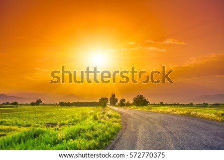 magnificent landscape of road on meadow on background of beautiful sunset sky with clouds. Exploring Armenia #572770375
