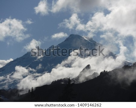Magnificent majestic mountain top, peaking above wispy clouds in Mount Baker, Washington. #1409146262