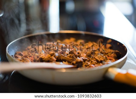 Magnificent nutritious organic dietary sliced chicken liver with a high content of protein and iron is actively fried with onions in a pan until it is completely ready before serving to the table #1093832603