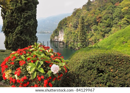 Magnificent park at the Italian villa-museum Balbyanello. Beautiful flower bed. Lake Como in the misty haze