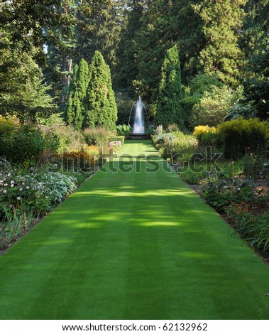 Magnificent park. Green grass road to the charming fountain