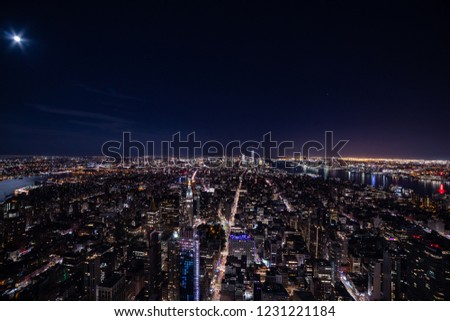 Magnificent skyline of a night New York.  Panoramic photo of midtown and Lower Manhattan with Easter and Hudson rivers. Moon shines in a dark sky #1231221184