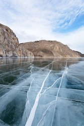 Magnificent smooth blue transparent ice with cracks on the frozen Baikal Lake on frosty day. A view from the ice to the rocks of the famous Sagan-Zaba cape with ancient rock paintings. Travel on ice