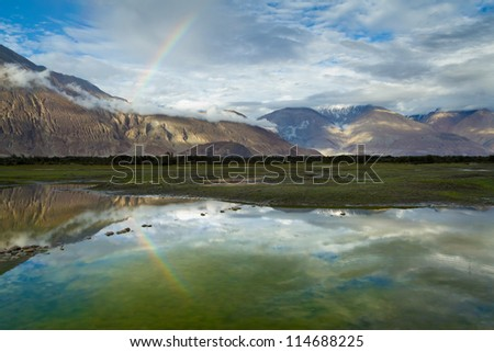 Magnificent sunset in the Nubra valley (Himalayas, India) with a rainbow after the rain.