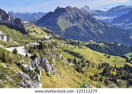 Magnificent Swiss Alps in early autumn. Green alpine meadows side by side with the first light snow