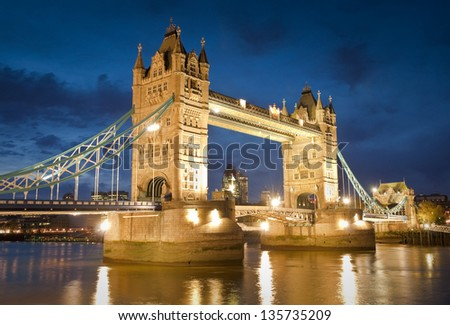 Magnificent Victorian Tower Bridge of London built in 1894 still stands as a symbol of the city. Converted brick warehouses and Thames beach and river illuminated by pretty night time lights.