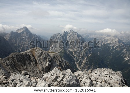 Magnificent view in Julian Alps. View from mt. Spik (2472 m) over the road to Vrsic pass. Mountains in the distance are Razor (left), Prisojnik and Mojstrovka (right). Haze typical for August. Stock fotó ©
