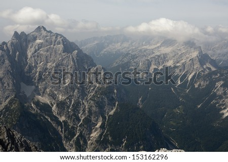 Magnificent view in Julian Alps. View from mt. Spik (2472 m) over the road to Vrsic pass. Mountains in the distance are Prisojnik (left) and Mojstrovka (right). Haze typical for August. Stock fotó ©