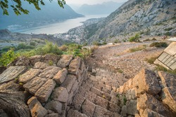Magnificent view over Kotor Bay from the top of a flight of old stone stairs which form the entrance to a stone hillside cottage overlooking the Old Town from far above.