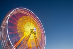 Magnificent views of amusement Ferris wheel against the blue sky with the inclusion of night lights