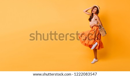 Magnificent woman in long bright skirt dancing in studio. Carefree inspired female model posing with pleasure on yellow background.