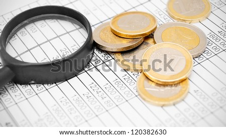 Magnifier and coins on documents.