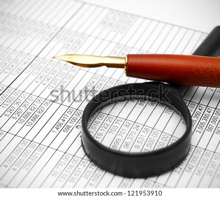 Magnifier and pen on documents.