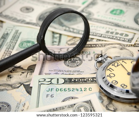 Magnifier and watches on dollars.