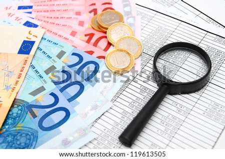 Magnifier, euro and coins on documents.