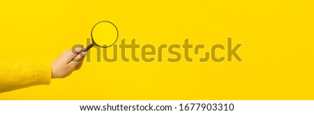 magnifier in hand  over yellow background, panoramic mock-up image Foto stock ©