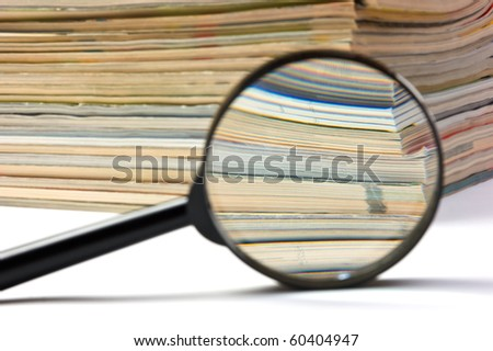 magnifier on the background of the stack of magazines