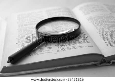 Magnifier on the open page of the English-Russian dictionary. The black-and-white image