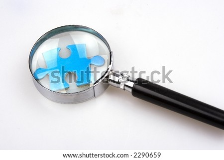 Magnifier over a piece of jigsaw puzzle.