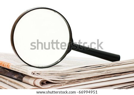 Magnify glass over a stack of newspaper - stock photo