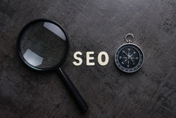 Magnifying glass, alphabet SEO and compass on dark cement background using as SEO Search engine optimization concept.