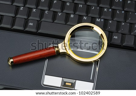 Magnifying glass and a laptop. The concept of search