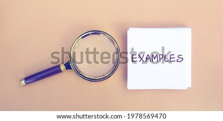 Magnifying glass and a note with the word Examples. Example, instance, sample. Business, marketing and training concept. Flat lay ストックフォト ©