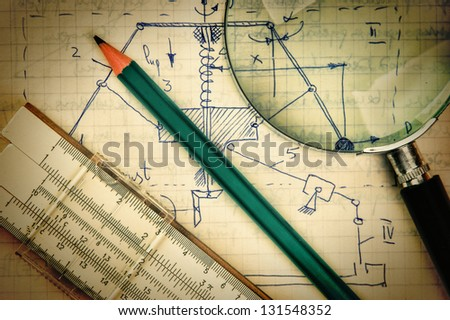 magnifying glass and a slide rule on the old page with the calculations in mechanics