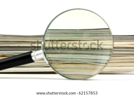 magnifying glass and a stack of magazines