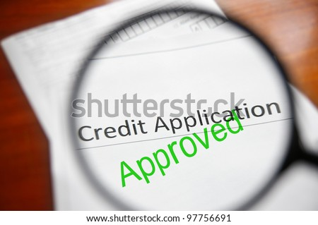magnifying glass and approved credit application form