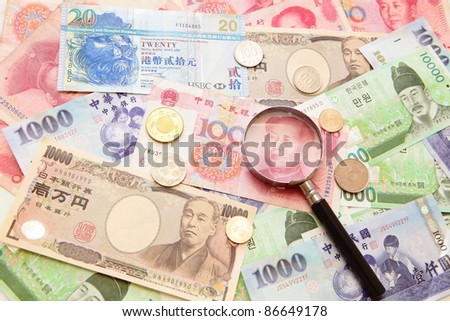 magnifying glass and Background of asian currency (include Korean Won, Taiwan dollar, Chinese Money yuan , Hong Kong Dollar, japanese Yen)
