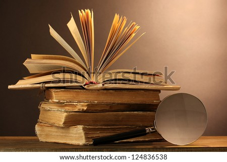 Magnifying glass and books on table