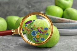 Magnifying glass and illustration of microbes on apple. Food poisoning concept
