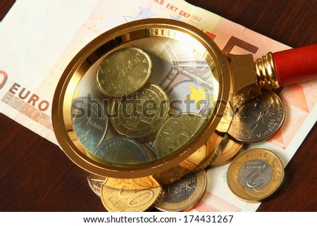 magnifying glass and money euro isolation on wood background