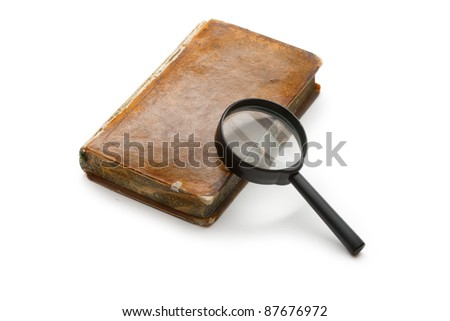 Magnifying glass and old book isolated on white