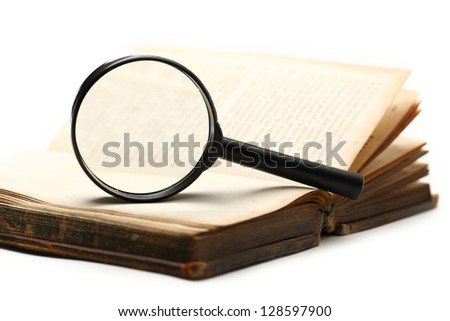 Magnifying glass and old book on the white background